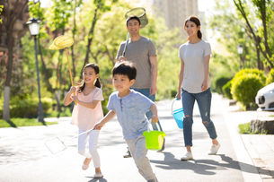 Happy young Chinese family with butterfly nets outdoorsの写真素材 [FYI02231572]