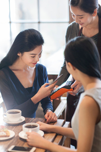 Chinese friends paying with smart phone in cafeの写真素材 [FYI02231577]