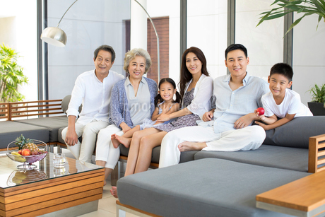 Happy Chinese family sitting on the sofaの写真素材 [FYI02231591]
