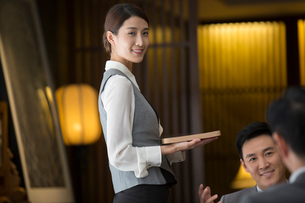 Elegance Chinese waitress holding a trayの写真素材 [FYI02231595]