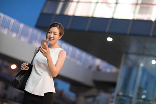 Cheerful young Chinese businesswoman using smart phoneの写真素材 [FYI02231600]