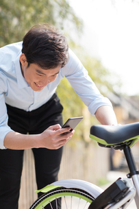 Young man scanning a QR code to unlock a share bikeの写真素材 [FYI02231623]