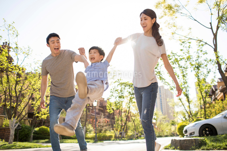 Happy young Chinese family playing outdoorsの写真素材 [FYI02231630]