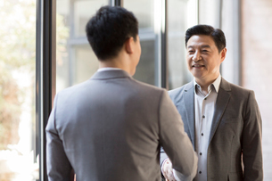 Confident Chinese businessmen shaking handsの写真素材 [FYI02231633]