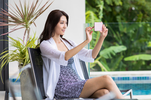 Happy young Chinese woman relaxing on balconyの写真素材 [FYI02231644]