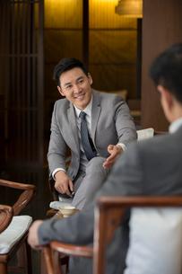 Cheerful Chinese businessmen talking in tea roomの写真素材 [FYI02231646]
