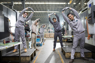 Engineers stretching in the factoryの写真素材 [FYI02231669]