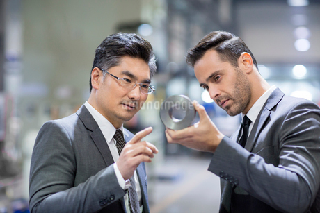 Business people checking machine parts in the factoryの写真素材 [FYI02231672]