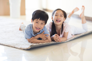 Cute Chinese children lying on carpet in new houseの写真素材 [FYI02231683]