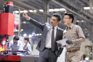 Businessman and engineer talking in the factoryの写真素材 [FYI02231688]