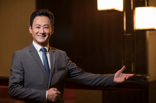 Confident Chinese hotel manager greetingの写真素材 [FYI02231689]