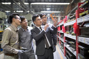 Businessman and engineers checking machine parts in the factoryの写真素材 [FYI02231697]