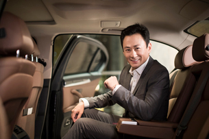 Successful Chinese businessman sitting in car back seatの写真素材 [FYI02231744]