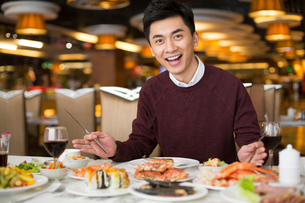 Cheerful young Chinese man having buffet dinnerの写真素材 [FYI02231753]
