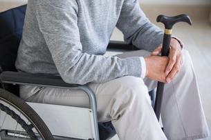 Senior man in wheelchair holding a caneの写真素材 [FYI02231755]
