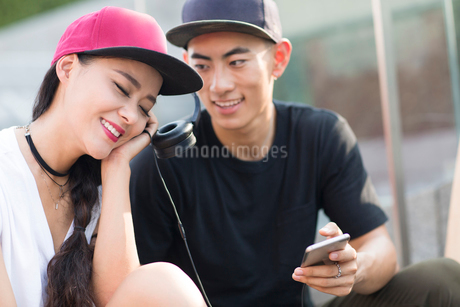 Cheerful young Chinese couple with skateboard listening to music on stairsの写真素材 [FYI02231761]