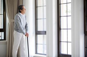 Senior man looking out windowの写真素材 [FYI02231762]