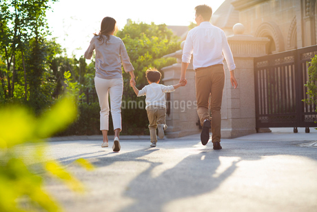 Happy young Chinese family holding hands runningの写真素材 [FYI02231763]