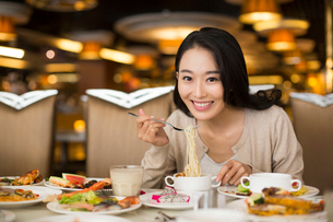 Cheerful young Chinese woman having buffet dinnerの写真素材 [FYI02231766]