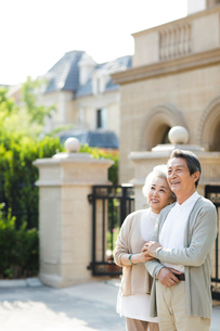 Cheerful senior Chinese couple standing in front of their villaの写真素材 [FYI02231789]