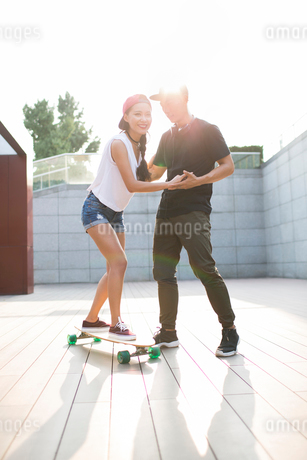 Young Chinese man teaching his girlfriend to skateboardの写真素材 [FYI02231792]