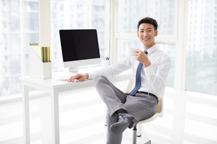 Cheerful young Chinese businessman taking a coffee breakの写真素材 [FYI02231801]
