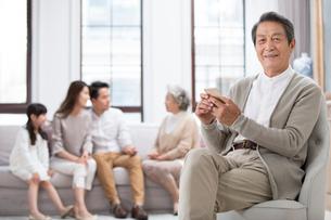 Senior Chinese man using smart phone at homeの写真素材 [FYI02231805]