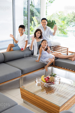 Happy young Chinese family relaxing on the sofaの写真素材 [FYI02231808]