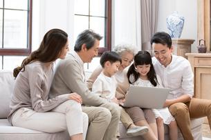 Happy Chinese family using laptop on sofaの写真素材 [FYI02231822]