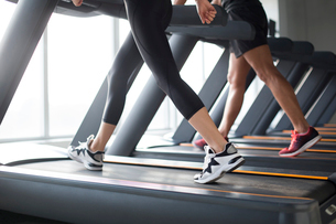 Young couple exercising on treadmills in gymの写真素材 [FYI02231829]