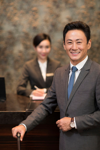 Cheerful Chinese businessman at hotel receptionの写真素材 [FYI02231845]