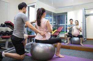 Pregnant woman working with trainer at gymの写真素材 [FYI02231846]