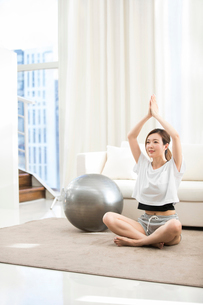 Young Chinese woman practicing yoga at homeの写真素材 [FYI02231860]