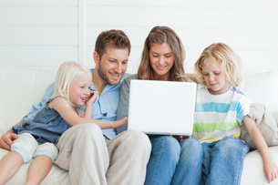 The family gather around the laptop to watch a good tv showの写真素材 [FYI02231866]