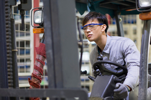 Young workman driving forklift in the factoryの写真素材 [FYI02231871]