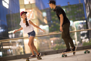 Cheerful young Chinese couple skateboardingの写真素材 [FYI02231882]