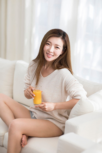 Cheerful young Chinese woman drinking juice on sofaの写真素材 [FYI02231883]