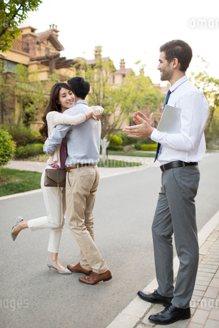 Happy young Chinese couple receiving house key from real estate agentの写真素材 [FYI02231894]