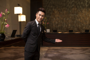 Confident Chinese hotel receptionist greetingの写真素材 [FYI02231907]