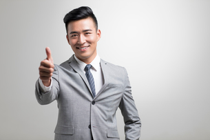Confident young Chinese businessman doing thumbs upの写真素材 [FYI02231937]