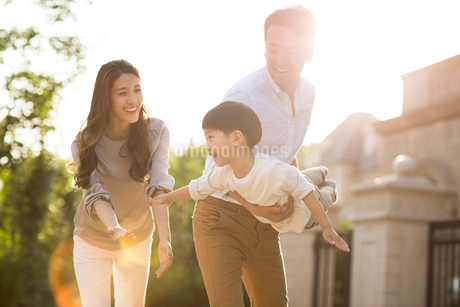 Happy young Chinese family playing outsideの写真素材 [FYI02231939]