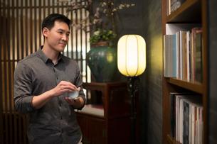 Mid adult Chinese man drinking teaの写真素材 [FYI02231967]