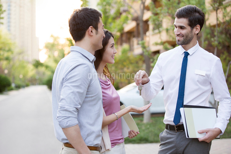 Happy young Chinese couple receiving house key from real estate agentの写真素材 [FYI02231983]