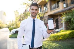 Confident businessman showing smart phoneの写真素材 [FYI02231998]