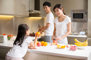 Happy young family cooking in kitchenの写真素材 [FYI02232000]