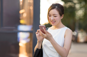 Cheerful young Chinese businesswoman using smart phoneの写真素材 [FYI02232007]