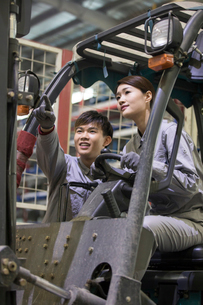Confident workers driving forklift in the factoryの写真素材 [FYI02232020]