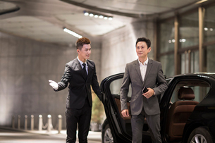 Chinese chauffeur opening car door for passengerの写真素材 [FYI02232021]