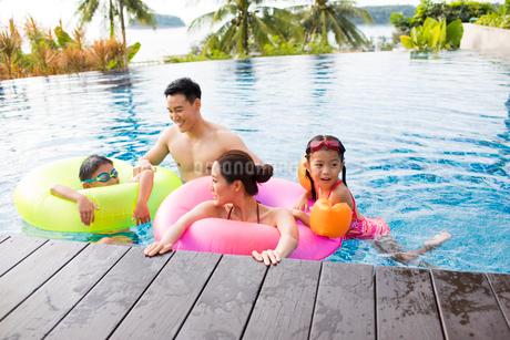 Happy young Chinese family having fun in swimming poolの写真素材 [FYI02232050]