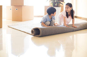 Cute Chinese children unrolling carpet in new houseの写真素材 [FYI02232056]